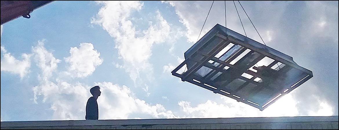 Air conditioning unit being lifted onto the roof of a building