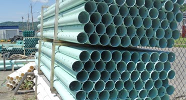 Pipes stacked by fence
